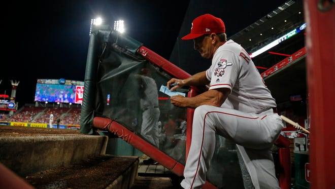 Cincinnati Reds interim manager Jim Riggleman (35) checks his notes in the dugout in the eighth inning of the MLB National League game between the Cincinnati Reds and the Chicago Cubs at Great American Ball Park in downtown Cincinnati on Friday, June 22, 2018. The Reds won 6-3.