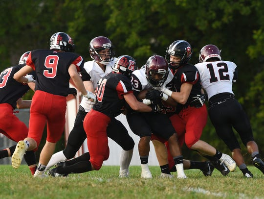 Rosecrans' Andrew Church and a teammate tackle Harvest Prep's Daniel Bangura earlier this season. Rosecrans hits the road in Week 11, opening the postseason at top-seed Danville.