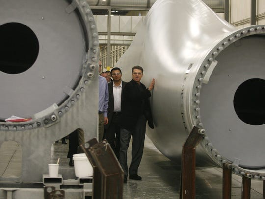 Texas Gov. Rick Perry examines the wind turbine blades