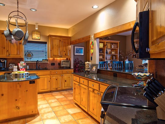 Beautiful natural finished wood cabinetry and an island topped with black granite compliments the kitchen which extends into the dining space.
