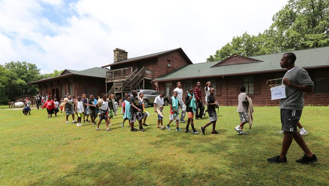 """Senior counselor Joshua Doty, right, holds the First Place award for """"clean cabin"""" at Camp Shurly, as the boys file out of the lunch room towards their cabins in 2014."""