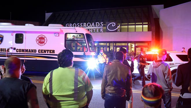 People gather in front of a north entrance to Crossroads Center Saturday night.