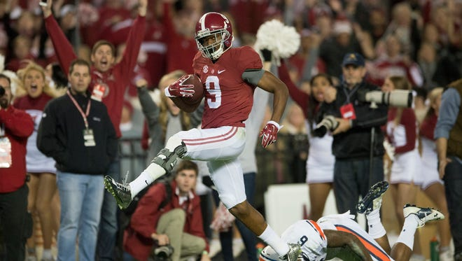 Alabama wide receiver Amari Cooper (9) scores a 75-yard touchdown reception as Auburn defensive back Jonathon Mincy (6) attempts to tackle him during the Iron Bowl at Bryant-Denny Stadium in Tuscaloosa, Ala., on Saturday, Nov. 29, 2014.