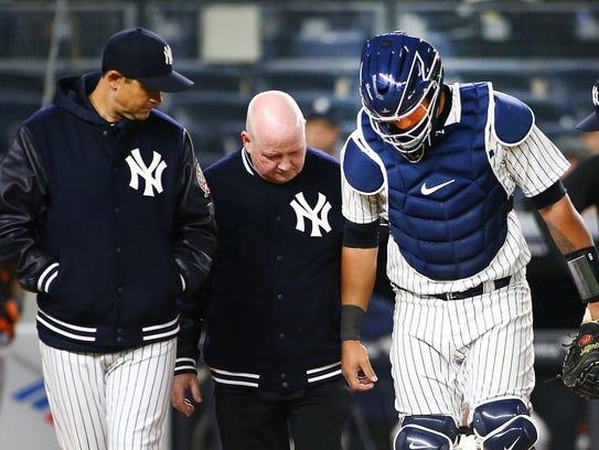 New York Yankees catcher Gary Sanchez (24) is helped