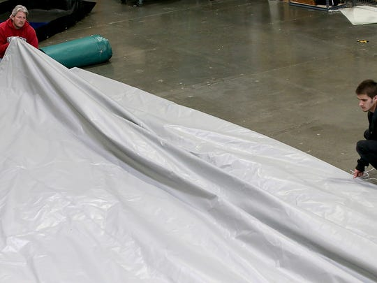 Rick Wood (left) and Nicholas Nordberg fold a custom garage tarp that they made at their Tarp Innovators in Poulsbo on Friday, June 8, 2018.