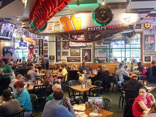 Diners eat dinner under an inverted race car at the newly opened Quaker Steak & Lube restaurant, Thursday, May 8, 2014, on Route 1 in Edison, NJ.  Jason Towlen/Staff Photographer