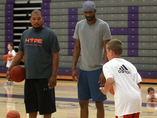 Corey Brewer (center) watches drills at his basketball