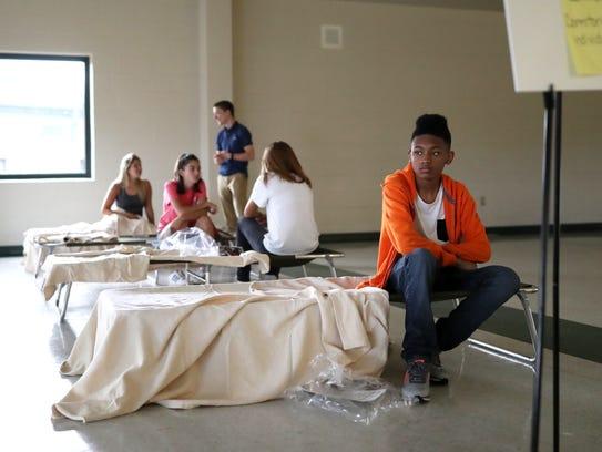 Volunteers, including Tyrrique Hudson, 17, check in