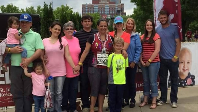 Gloria Gant stands with her family and cheering section after having run the half-marathon at the Rock 'n' Roll Marathon in Nashville last year. She's running it again this year despite going through extensive jaw surgery late last year and still recovering from it.