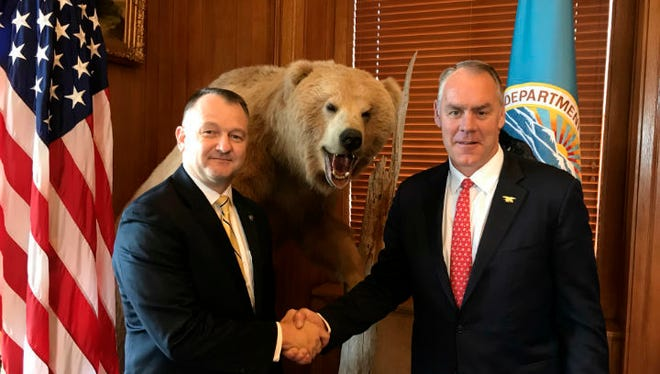 """This undated photo provided by the National Park Service shows Secretary of the Interior Ryan Zinke, right, congratulates Cameron """"Cam"""" Sholly who was named the new superintendent to Yellowstone National Park, on Wednesday, June 13, 2018 in Washington. (National Park Service via AP)"""