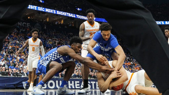 As a referree watches, Kentucky surrounds Tennessee's Grant Williams during a loose ball scramble in the Wildcats' 77-72 win over Tennessee Sunday in St. Louis for the SEC Championship. March 11, 2018