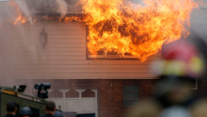 Firefighters put out a house fire in the 900 block of West Ildereen Street on Tuesday, July 12, 2016. Police believe a man was in the house.