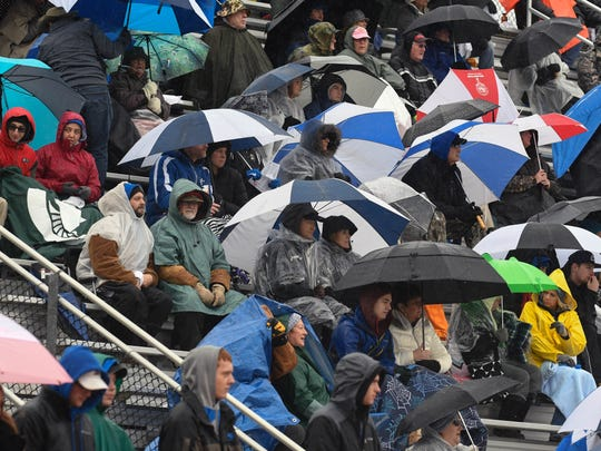 Harper Creek fans brave a steady rain to cheer on their team  during Saturday's  game against Muskegon.