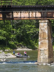 A boat arrives at the rock in the Winooski River where
