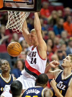 Portland Trail Blazers forward Mason Plumlee, center, dunks over Utah Jazz center Tibor Pleiss during the first half of an NBA preseason basketball game in Portland, Sunday.
