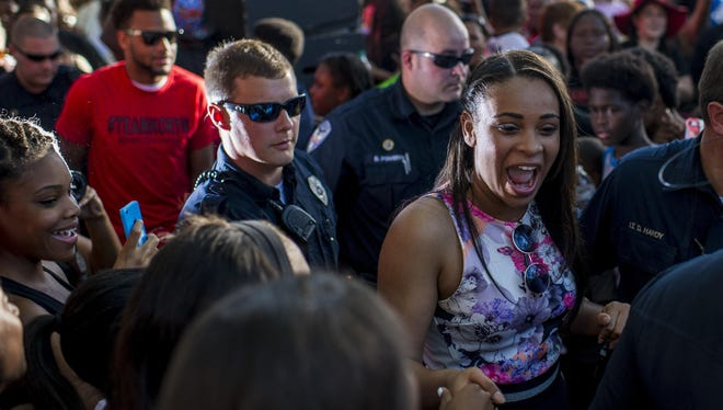 Koryn Hawthorne, an Abbeville native and competitor on the NBC television music series 'The Voice', is escorted into Magdalen Square for a performance May 6 in downtown Abbeville.