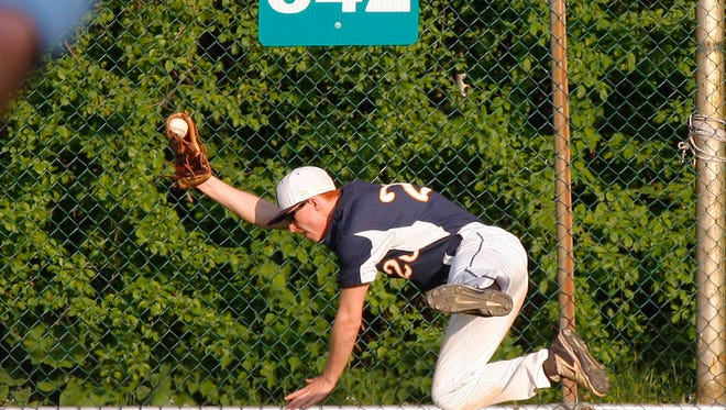 DeWitt's Josh Robinson makes a diving catch at the fence to end the game against Portland Tuesday, May 24, 2016, at Kircher-Municipal Park.