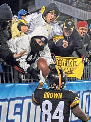 Steelers wide receiver Antonio Brown give a ball to a fan after scoring a touchdown in the fourth quarter Monday.