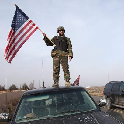 A man waves an American flag from atop a car at the Narrows roadblock near Burns, Oregon, Thursday. The last four occupiers of a Malheur National Wildlife Refuge in eastern Oregon surrendered Thursday.
