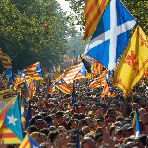 Demonstrators pushing for a secession vote for the Spanish region of Catalonia, some waving Scottish flags to support that independence vote, march in Barcelona on Sept. 11.