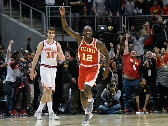 Atlanta Hawks forward Taurean Prince (12) reacts as Phoenix Suns forward Dragan Bender (35) looks on as an NBA basketball game comes to an end Sunday, March 4, 2018, in Atlanta. (AP Photo/John Amis)