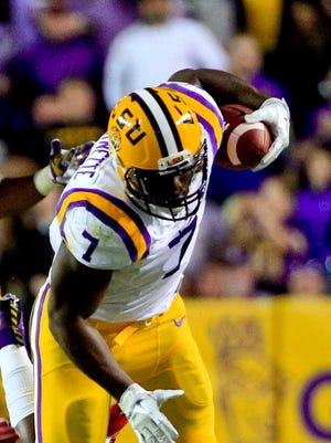 LSU Tigers running back Leonard Fournette (7) runs over Mississippi Rebels defensive back Deontay Anderson (2) during the first quarter of a game at Tiger Stadium.