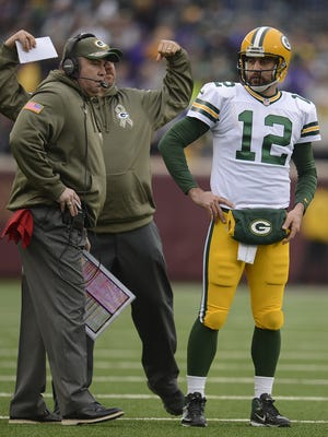Green Bay Packers quarterback Aaron Rodgers talks with coach Mike McCarthy during a timeout in Sunday's game against the Minnesota Vikings at TCF Bank Stadium in Minneapolis.