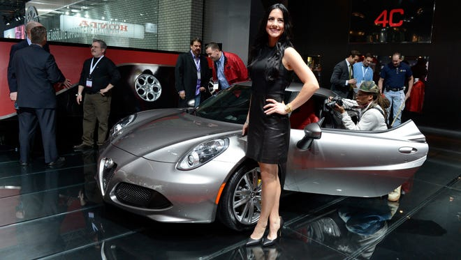 Product Specialist Chelsea Duda of Rochester Hills, Michigan, stands next to the Alfa Romeo 4C on display during Wednesday's press preview day at New York International Auto Show at the Jacob K. Javits Convention Center in New York.