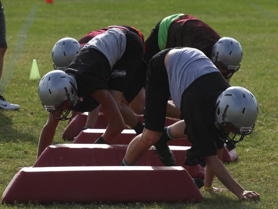 Players are on all-fours as they drill during football