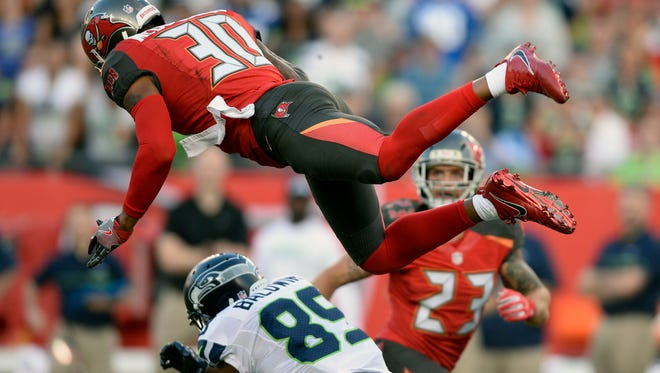 Seattle Seahawks wide receiver Doug Baldwin (89) loses the football as he is hit by Tampa Bay Buccaneers free safety Bradley McDougald (30) during the second quarter Sunday. McDougald was called for pass interference on the play.