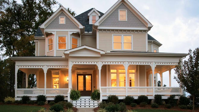 Bay windows and decorative trim showcase Victorian-style flair on the exterior.