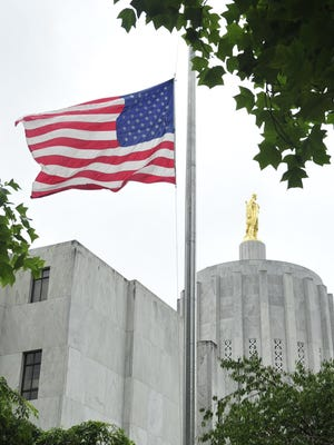 In this 2011 file photo, the flag at the Oregon State Capitol flies at half mast. Flags on public grounds are at half mast this week after a Tuesday proclamation from President Barack Obama ordered them lowered out of respect for the five soldiers who were killed in attacks at Chattanooga military recruiting stations last week.