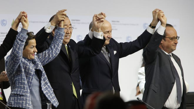 World leaders celebrate the adoption of a climate pact on Dec. 12, 2015.