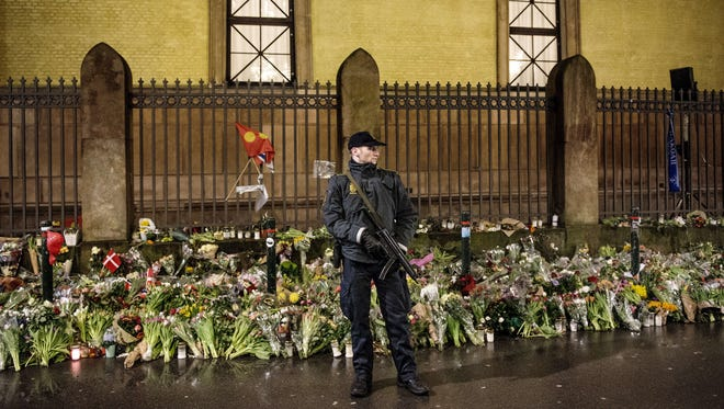 An armed police officer guards a Jewish synagogue during a memorial service in Copenhagen on Feb. 24 for Dan Uzan and Finn Noergaard, who were killed during twin terrorist attacks.