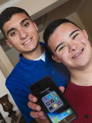 Andrew West/The News-Press Johnny Ciocca, 17,left, a junior at Estero High School, has written over 30 apps in the last several years. He specializes in apps that help families with children who have special needs connect socially and improve their  lives. On the right is his older brother, Christian, who has Down Syndrome. Johnny Ciocca, 17,left, a junior at Estero High School has written over 30 apps in the last several years. He specializes in apps that help families with children who have special needs connect socially and improve thier lives. On the right is his older brother, Christian, who has Down Syndrome.