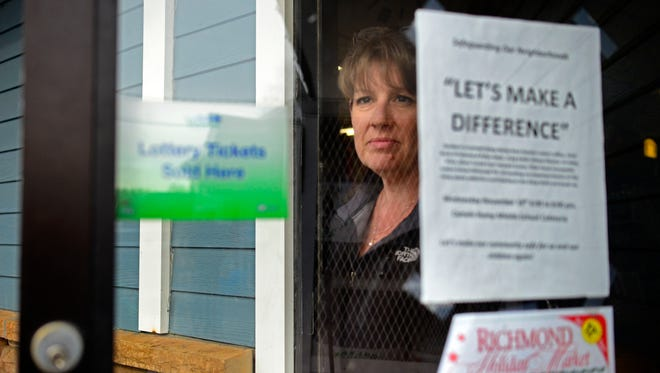 """Linda Donovan looks out the front door of the Lucky Spot on Sunday, November 15. On the door is one of the original flyers made for the community forum, which says """"Let's make a difference."""" The Donovans later changed the flyer to say """"We are being victimized."""""""