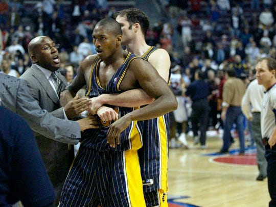 Austin Croshere tries to hold Ron Artest back following