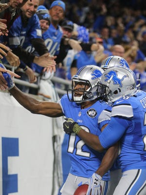 Lions punt returner Andre Roberts slaps hands with some fans to celebrate his touchdown.