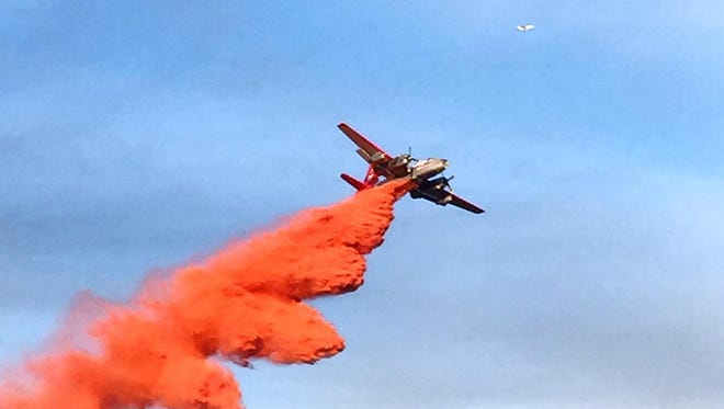 A plane drops fire retardant over the Blevens Fire, which burned 28 acres near Globe as of Thursday afternoon.