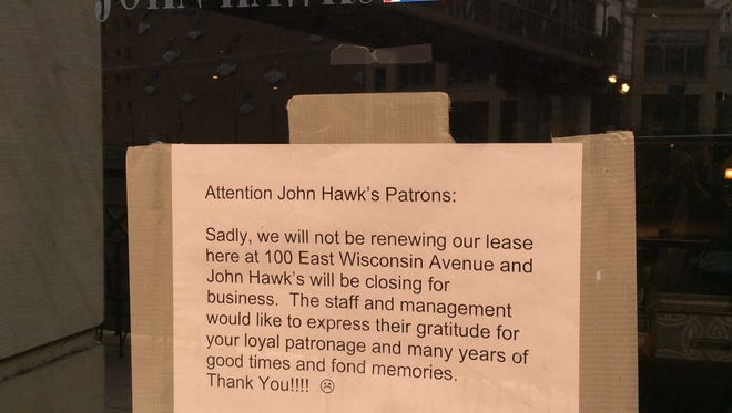 A sign posted on the doors and windows at John Hawks Pub, 100 E. Wisconsin Ave., says the restaurant has closed.