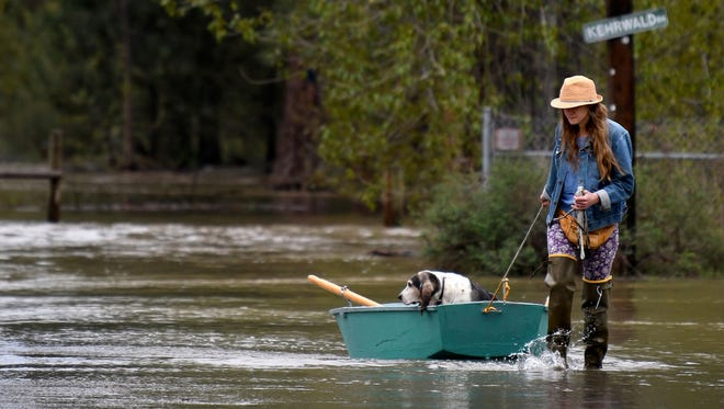 Katie Condon ferries her 13-year-old basset hound, Fran, for a respite from the floodwater surrounding her home at the north end of Tower Street on the outskirts of Missoula, Mont., Monday, May 7, 2018. (Kurt Wilson/The Missoulian via AP)