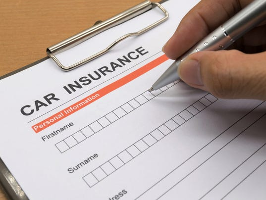 man signing a car insurance policy