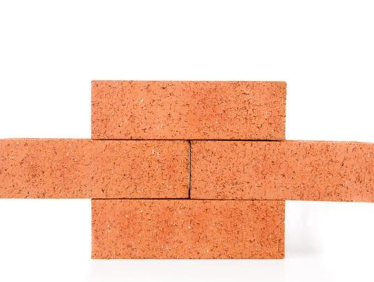 Four clay bricks building a wall