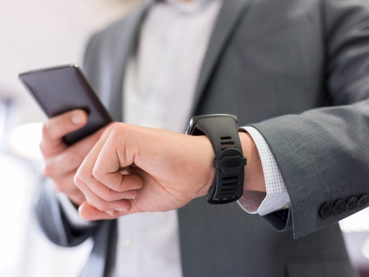 Modern businessman focused on his phone and smart watch