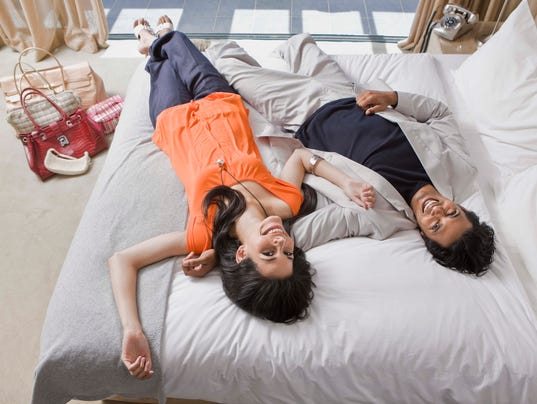 Couple laughing and lying on bed in hotel room