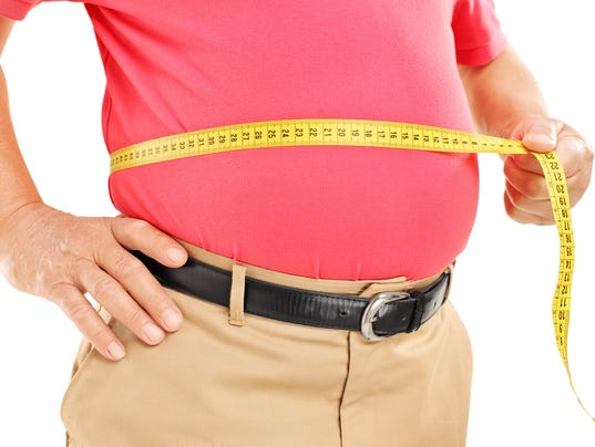 Fat mature man measuring his belly with tape
