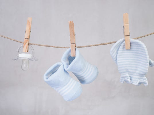 Baby goods hanging on the clothesline with clothespins