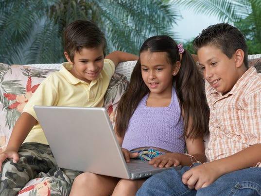 Two boys and a girl sitting in front of a laptop