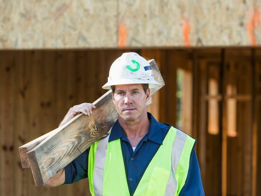 Construction worker at a job site carrying lumber