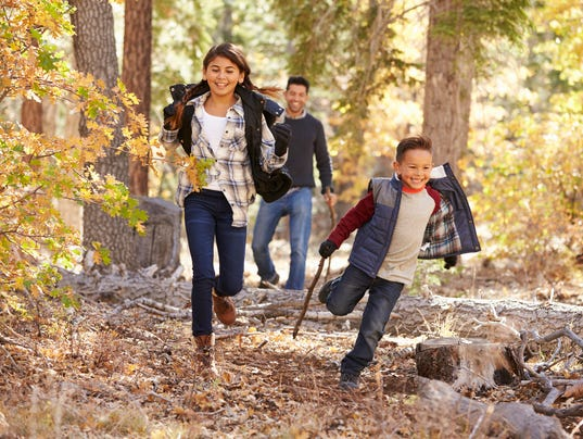 Children in a forest running to camera, father looking on
